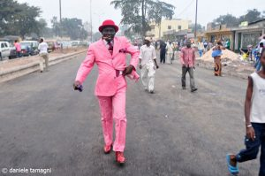 an image from Tamagni's book that displays a sapeur donning a bright pink suit, pink hat, and pink shoes with a cigar in his mouth struts on a dusty concrete road with cars passing on his left and regularly dressed people behind him.