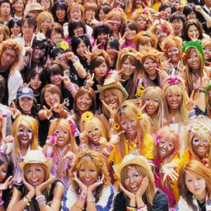 Image of a group photo of ganguro girls and boys. Most of them have dyed blonde hair and intense make-up with white eyeshadow.