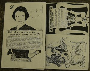"A black and white photograph of two pages from an open Riot Grrrl zine. The title of one of the pages reads ""The D.C. March for Women's Lives"" with a black and white image of a determined-looking woman with a hand on her hip. The other open page shows an abstract depiction of a naked woman and a line drawing of the upper half of a naked woman. Both images are surrounded by indistinguishable text."