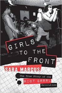 A picture of the book Girls to the Front: The True Story of the Riot Grrrl Revolution by Sara Marcus with a black and white picture of a women singing with women playing the guitar and drums in the background.