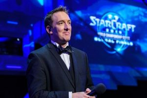 """A picture of Paul Chaloner in a suit, looking proud. Behind him is a screen that says """"STARCRAFT."""""""