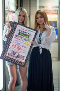 Two high school gyaru girls with their hair died blonde and uniform white shirt tied up stylishtically