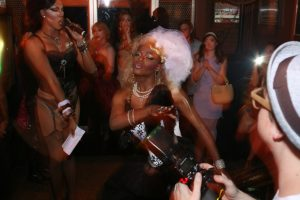 2 Black drag queens are dancing at a ball. They are wearing fitted black tops and garter tights. One queen has a white and blond wig on.