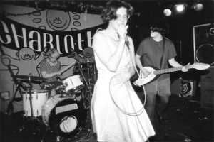 A black and white image of a woman in a dress and glasses singing into a mircophone. Another band member in the background is playing the electric guitar while another woman plays the drums.