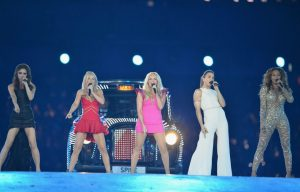 An image of the five members of The Spice Girls standing in a line onstage, each singing into a microphone. There are bright lights and a bedazzled car in the background.