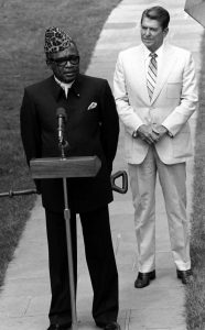 President Mobutu has on a leapord print traditional hat that points upwards in a triangularesque fashion. His Mao-like tunic is distinct for the collar, which looks like an elongated shirt-dress color attached to a coat. In contrast, President's suit is a traditional Western suit, worn with a collared dress shirt and complete with a tie.