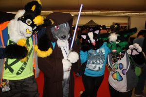 Four furries wearing fursuits are pictured at a convention. They are doglike and catlike in appearance, and all are wearing t-shirts. Image URL: https://c2.staticflickr.com/8/7284/9754655266_60243d2db0_b.jpg