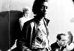 This is a black and white picture of Karla Mad Dog standing in the center, facing the camera, with her hands in her pockets. Behind her, slightly to the left is another band member with their back against the wall, folding their arms. In the bottom right corner of the photo, is the head of the third members, who appears to be sitting down. His face cannot be fully seen.
