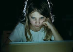 Young girl staring intently at a lit computer screen in a dark room
