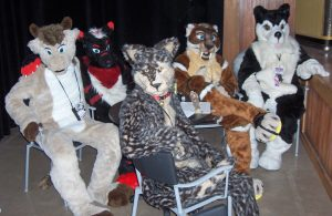 Five furries wearing fursuits, mostly canid in nature, sitting in chairs at a convention. Image URL: https://upload.wikimedia.org/wikipedia/commons/b/be/Anthrocon_2007_Furry_Tales_fursuit_table.jpg