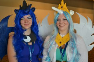 Image of two people dressed up as My Little Pony characters. The two people have colorful wigs on, wings, and horns.