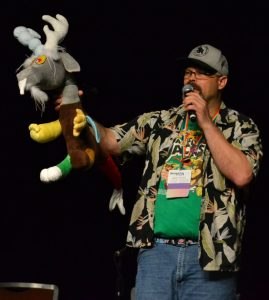 Image of Dustykatt speaking at Bronycon while holding a My Little Pony plush toy