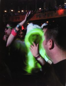 Photo depicts a man in a white hood with a glowing green trim. He is shown giving another man a high-five.