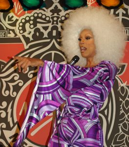 RuPaul is dressed in drag, in a technocolored purple dress with a huge hit afro. She is pointing at something and holding a microphone.