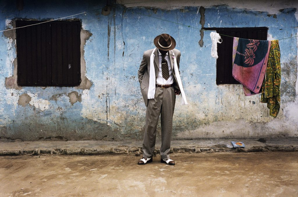 A sapeur wearing a three-colored coordinated suit of ash brown, white, and dark brown. His face is hidden by a wide-brimmed brown hat as he stares towards his designer leather shoes. His figure and attire is in stark contrast to the faded wall of a dilapidated structure behind him. The dirt road he stands on is dusty and there is a makeshift laundry string hanging above his head with towels.