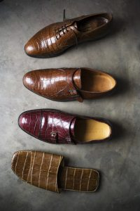 displays four types of the luxury crocodile shoes, which are made from crocodile skin and distinct for the scaly pattern. The styles and colors of the shoes vary, one being a maroon colored dress shoe, a brown sandal, and two types of bronze colored dress shoes.