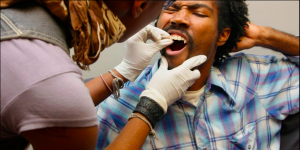 Woman putting custom-made fangs onto the teeth of a male customer.