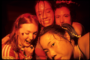 Photo depicts an L.A. rave with four girls smiling in the photo. They are all wearing glitter on their faces and there is a black background.