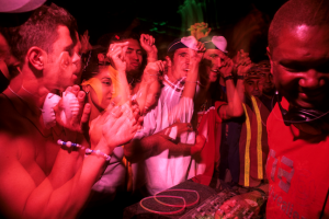 Image depicts a DJ with rave goers dancing by his booth.