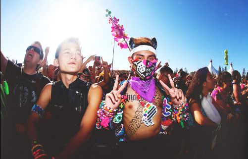 Photo depicts a San Francisco rave. A person with a pink patterned mask and other colorful accessories is posing with his hands in a peace sign. The background depicts other concert goers and a blue sky. Photo taken by Chromat Media Photogaphy.