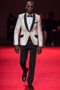 """one of Watanabe's models walking down the red carpet with a more """"traditional"""" white dress shirt and black pants and shoes. The reminiscent quality of sapeur fashion is found in the nuances of the jacket, adherence to the """"three-color"""" rule, and general atmosphere of the model. He  wears circular sunglasses, a black bowtie, and a white gold metallic jacket with black lapels, pocket covers, and handkerchief pocket."""