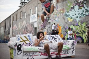 A skater does a trick over a couch while another man sits on the couch. The couch and the walls behind it are covered in graffiti.