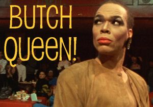 Paris Duprée with drag makeup on and a brown shirt. She is looking up and to the left. The words Butch Queen are in bold on the left of the photo.