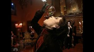 A man wearing black and red Goth clothing drinking blood from a wine glass.