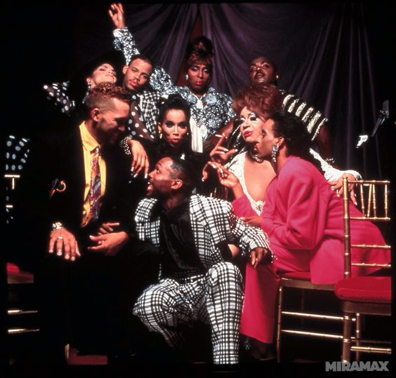 Cast of Paris is Burning, some dressed in drag other in suits. All gathered together making dramatic faces at the camera.