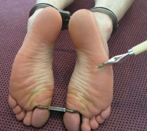 Two white feet cuffed together at the ankles, and then also cuffed at the big toes. Someone (off-screen) holds something sharp towards the bottom of the right foot.