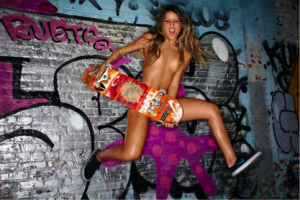 A female skater is jumping in the air, completely naked, holding a skateboard in front of her private parts.