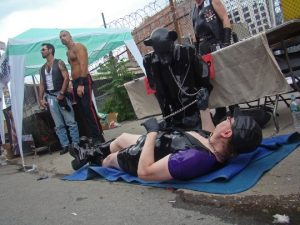 man wearing leather lays down on the floor holding the leash of a man dressed in a full puppy play leather outfit. Others stand in the background at this outside street festival.