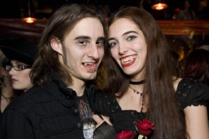 A man and woman wearing all black smiling and showing their fangs.