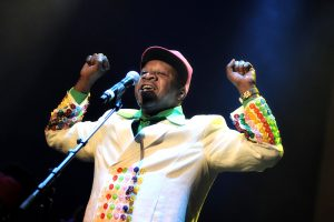 Papa Wemba performs in front of a microphone, his hands theatrically popped up at his sides. He is wearing a cap, pale yellow suit jacket with multi-colored buttons all over the cuffs and the front of his jacket.