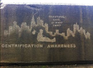 """A reverse graffiti piece that reads """"BEAUTIFUL CITY, AT WHAT COST? GENTRIFICATION AWARENESS"""""""