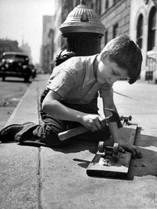 A young boy working on his skateboard in the street