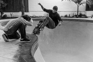 A professional skateboarder, Lance Mountain, skating in an empty pool