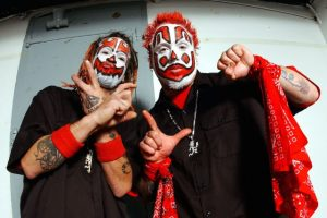 Photo of ICP members Shaggy 2 Dope and Violent J in clown makeup, died red hair, and black and red outfits. They are holding up piece signs and fists.