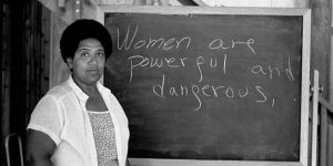 "A black and white photograph of Audre Lorde standing in front of a blackboard that has ""Women are powerful and dangerous"" handwritten across it in chalk."