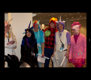 An image of six bronies dressed as characters from the show. Four of the fans are male. Each of the fans is dressed in a different costume involving bright colors, pony ears, and a unicorn horn.
