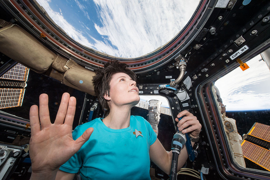 A picture of the astronaut Samantha Cristoforetti performing a Vulcan salute while in orbit, with the Earth in the background
