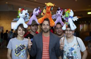 Image depicts five young men with My Little Pony plush ponies on their heads. Picture was taken at the Bronie event BUCK 2013 in Manchester.