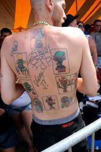 In this photo, a man's back is facing the camera. He has nine Juggalo Joker tattoos, each in different colors.