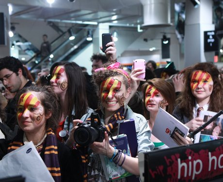The photo depicts a group of female Harry Potter fans with red and yellow face paint. One girl is holding a camera and looking directly at the photographer.