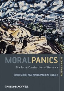 A book cover of Moral Panics the Social Construction of Deviance with people running down a mountain toward a village. The picture uses dark colors and is drawn abstractly.