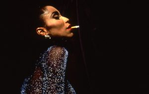 The image displays a drag queen with a cigarette in her mouth wearing a sparkly dress. The background is black.