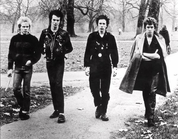 A black and white photo of four punks walking down the street in full punk style