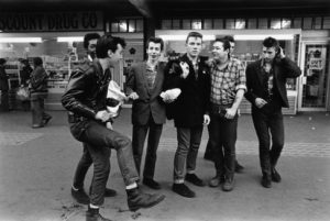 The black and white photo depicts a group of Teddy boys dancing and hanging out outside of a store. There are seven young men in the frame and one is posed with his leg raised.