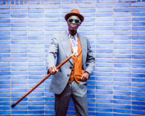 man with blue sunglasses, brown hat, gray pinstripe suit, colorful shirt and brown vest