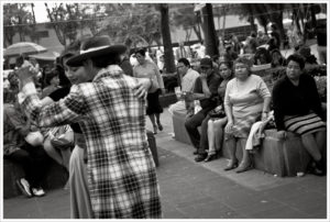 Black and white photo of Pachuco dancing in a square in Mexico while onlookers observe.
